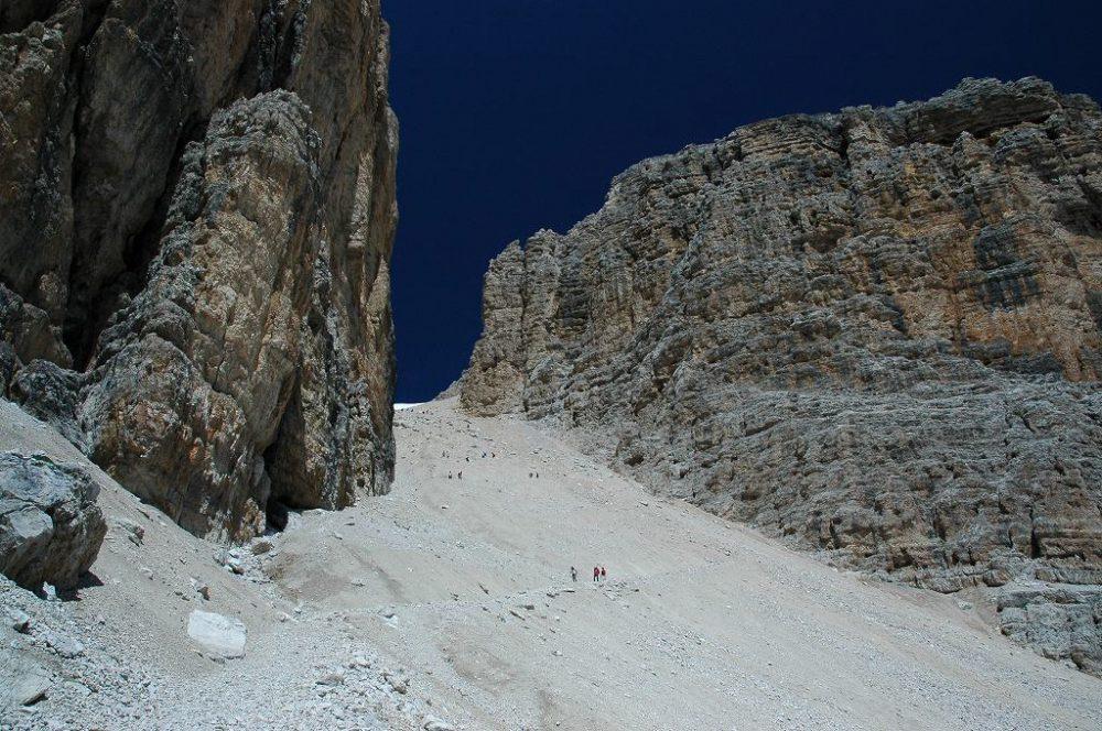 ドロミテの歩き方。ドロミテの展望台・サス・ポルドイ(2,950m)~パッソ・ポルドイ(2239m)トレッキング。フォルチェラ小屋はもう見えません。グルッポ・デル・セッラの岩壁が迫って