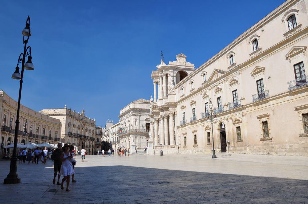 シチリア、シラクーサ、ドゥオーモ広場。女性が歩き始めた方向、広場の奥にカラヴァッジョの「サンタルチアの埋葬」が見られる教会がある