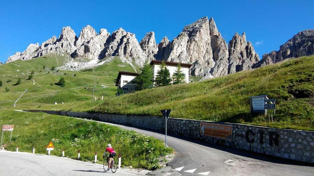 ガルデナ峠でCIR背景に自転車で登る女性が
